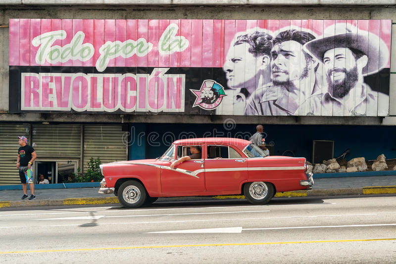 Vintage car next to a poster supporting the Cuban Revolution in stock images