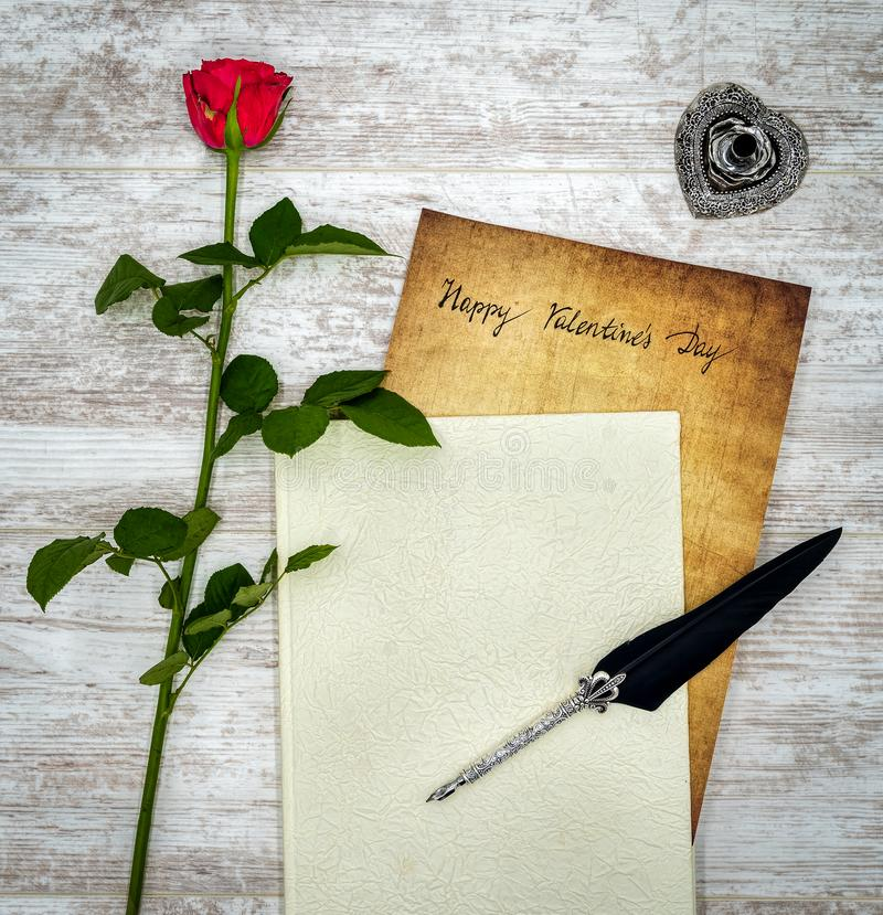 Vintage card with red rose, white book, ink and quill on white painted oak - top view royalty free illustration