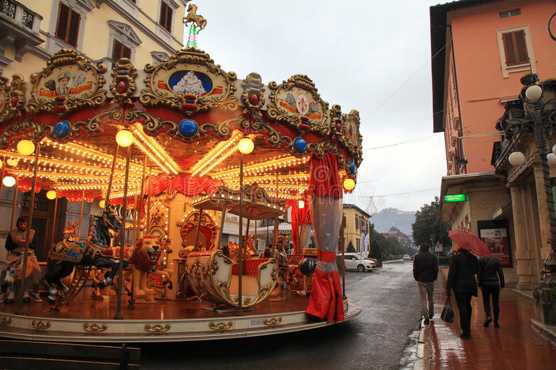 Vintage carousel on the street in rainy winter day, Italy. MONTECATINI-TERME, ITALY - JANUARY 8, 2016: Vintage carousel on the street in rainy winter day stock images