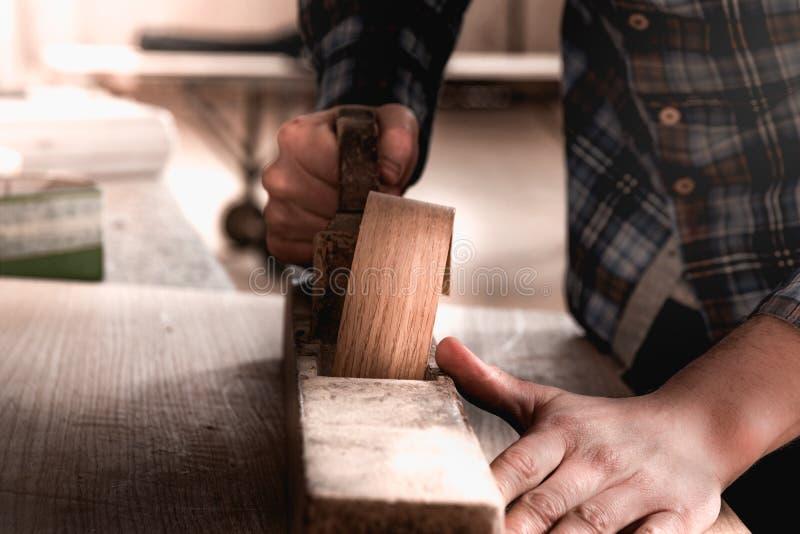 Vintage carpenter working on wood using wood retro vintage old ancient planer. Workshop background stock photography