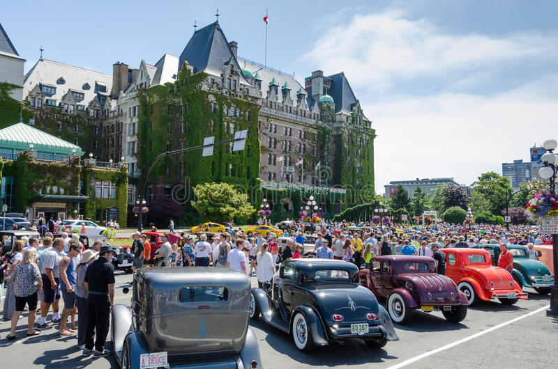 Vintage cars parked in front of the Empress Hotel. Crowds inspect vintage cars including popular1932 Ford Coupes parked in front of the Empress Hotel during stock images