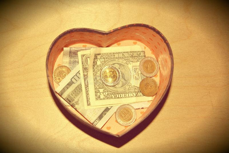 Save money. Vintage saving Cash in a box heart shaped money usd dollars coins money change royalty free stock photo