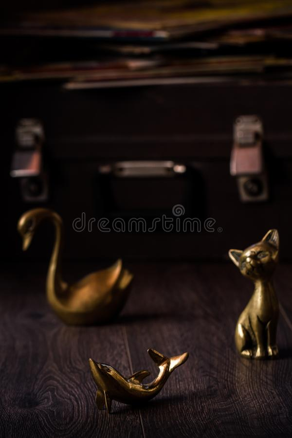 Vintage Cat, Dolphin and Swan Brass Figurines on Brown Background stock photography