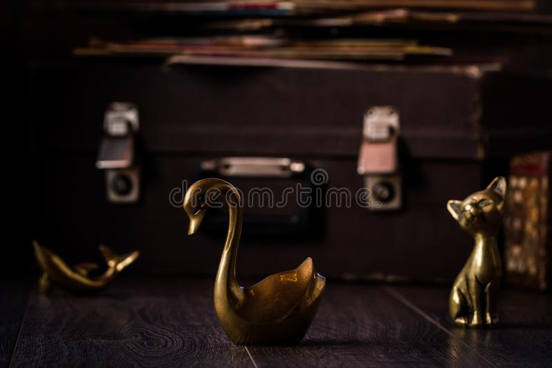 Vintage Cat, Dolphin and Swan Brass Figurines on Brown Background royalty free stock photography