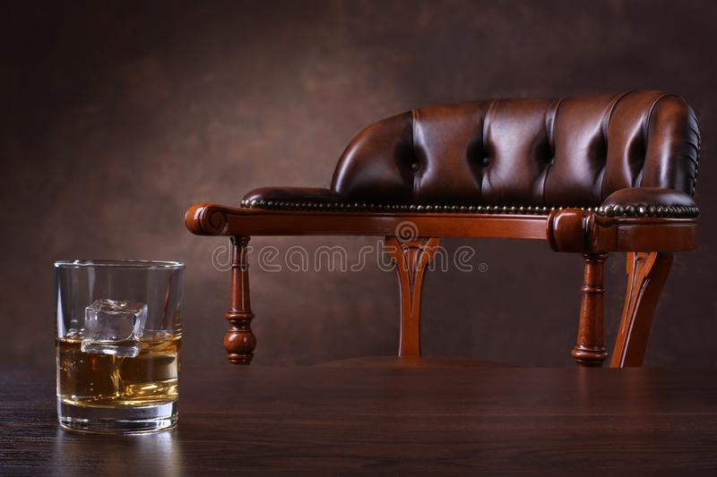 Vintage chair and glass of whiskey on wooden table royalty free stock image