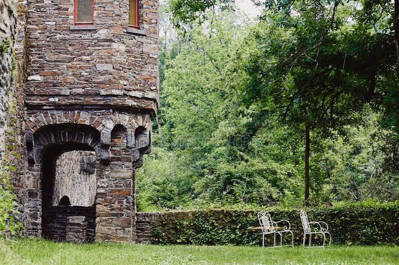 Vintage chairs outdoor in courtyard of medieval castle. Two vintage white chairs outdoor in green courtyard of medieval castle royalty free stock photos