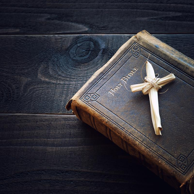 Vintage Christian Leather Bible Still Life with Cross made of grass reeds on Dark Wood Board Background. Square. Crop with looking down from above view stock photography