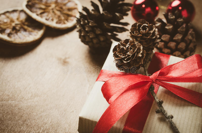 Vintage Christmas background. Kraft boxes with gifts, tied with red ribbons and pine cones in rustic style. royalty free stock photo