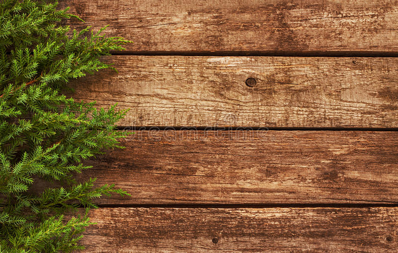 Vintage christmas background - old wood and pine branch. Vintage christmas background - old planked wood board with pine tree branch royalty free stock images