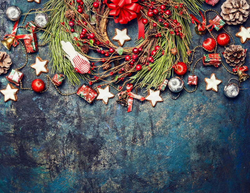 Vintage Christmas background with red decoration, wreath of red winter berries and cookies, top view. Horizontal border royalty free stock image