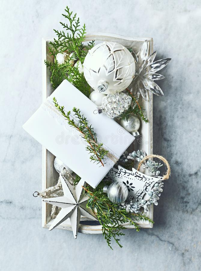 Vintage Christmas Decorations, gift box and Evstmas Decorations and Evergreen Twigs on a rustic wooden tray. Flatlay. Copy space stock images