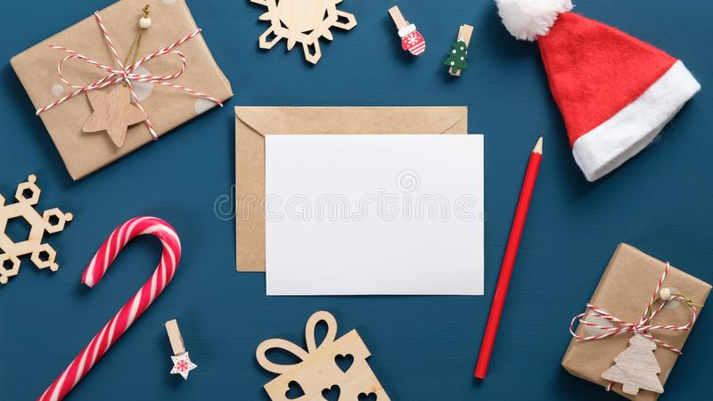 Vintage Christmas elements set. Flat lay retro wooden decorations, candy cane, New Year hat, gift boxes wrapped craft paper,. Envelope with blank white card stock photo