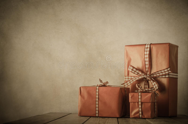 Vintage Christmas - Gifts on Table. Vintage style image of gifts wrapped in paper and tied with gingham ribbon on a wood planked table with parchment background stock photography