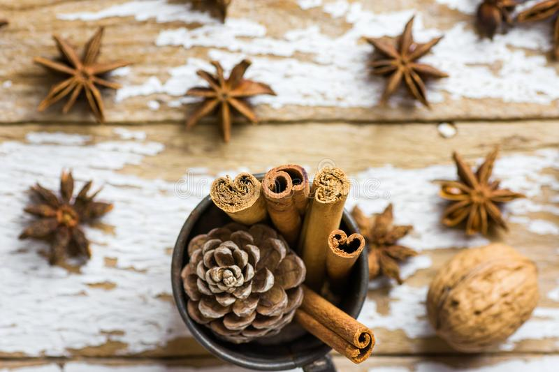 Vintage Christmas Greeting Cad with Baking Ingredients Decoration Cinnamon Sticks Anise Stars Pine Cones in Jug on Snowy Wood stock image