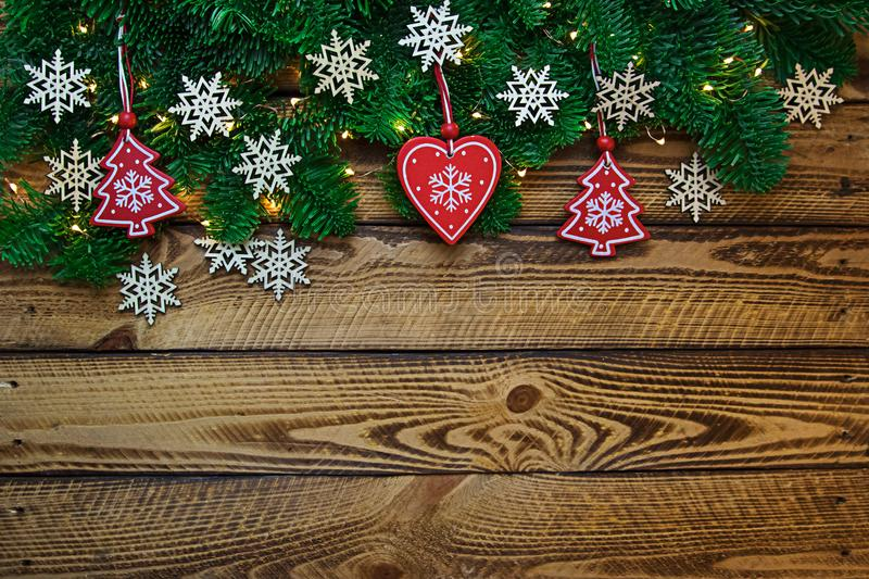Christmas holidays background with fir tree branches and snowflokes over wooden planks stock image