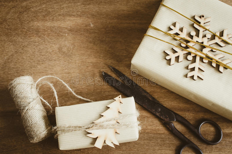 Vintage Christmas Kraft Boxes with Gifts Decorated in Rustic Style and Old Vintage Scissors on Wooden Background. stock photos