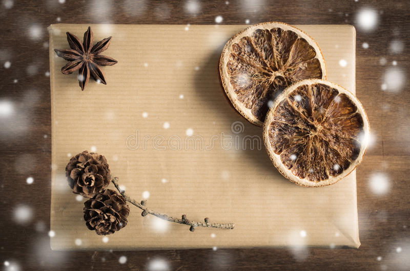 Vintage Christmas Kraft Gift Box in Rustic Style Decorated with Cones and Dried Orange Slices. Snow Falling Effect. royalty free stock photography