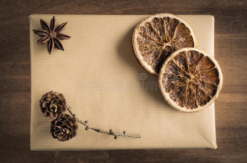 Vintage Christmas Kraft Gift Box in Rustic Style Decorated with Cones, Star Anise and Dried Orange Slices. stock image