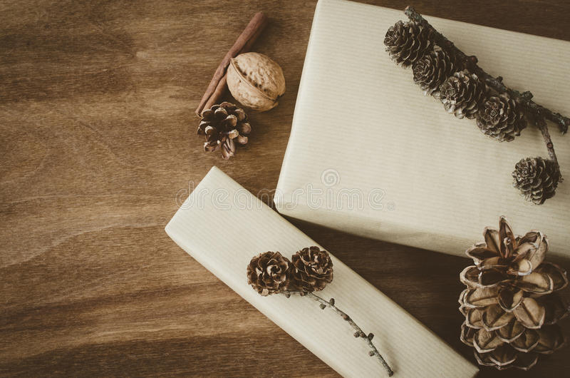 Vintage Christmas Kraft Gift Box in Rustic Style Decorated with Pine Cones on Wooden Background. royalty free stock photography