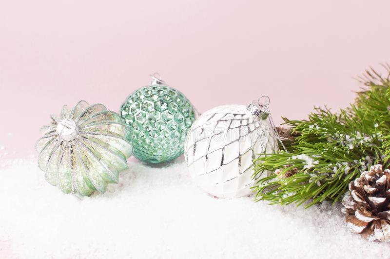 Vintage Christmas New Year balls in the snow and pine branches on pink background Flat Lay copy space. Holiday Baubles, beautiful royalty free stock image