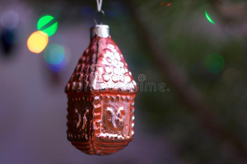 Vintage christmas tree toy house of glass on pine at night with lights closeup royalty free stock photo
