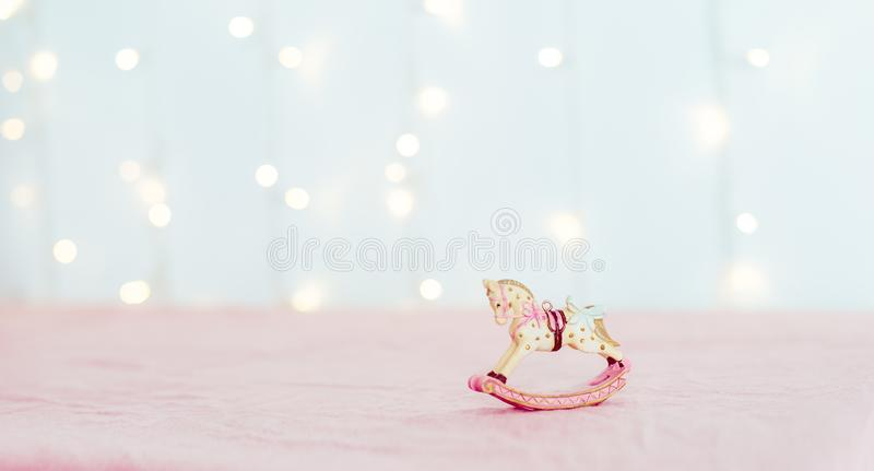 Vintage Christmas tree toy porcelain figurine of a rocking horse standing on the pink tablecloth against the background of blurred stock photos