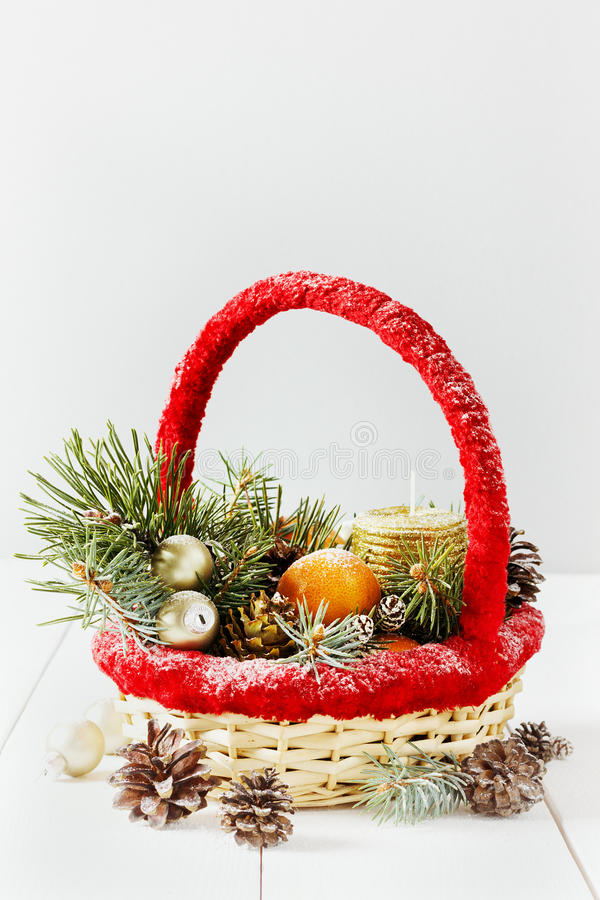 Vintage christmas or xmas composition. basket with tangerines, pine cone, golden balls, fir branches and candle stock photos