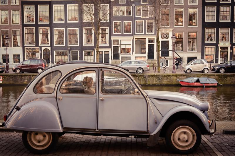 Vintage Citroen 2CV parked along a canal in Amsterdam Netherlands. March 2015. stock photos