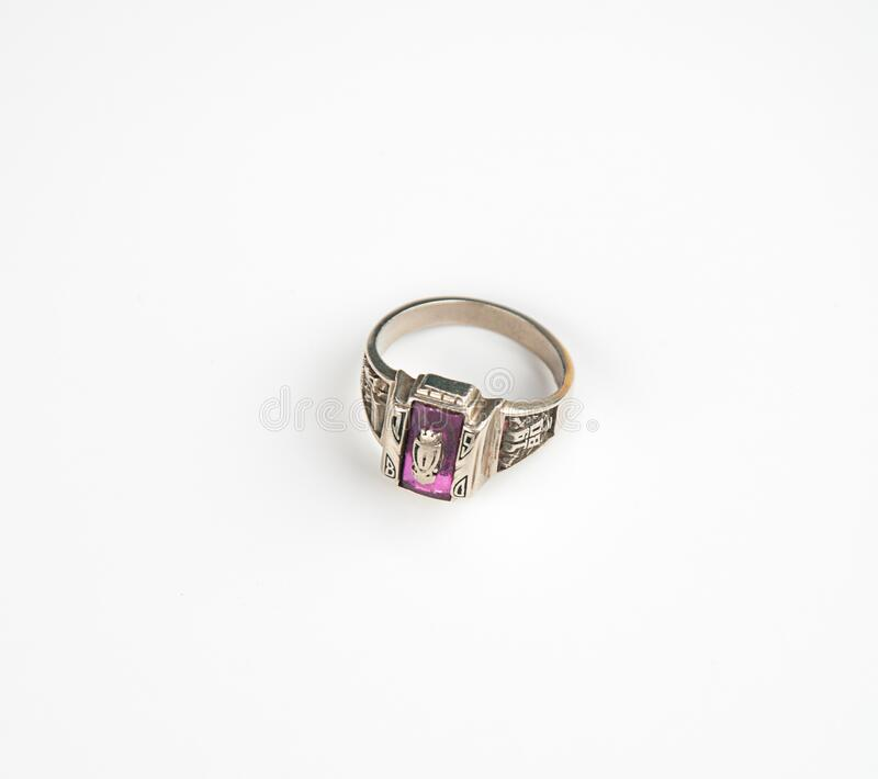 Vintage 1980 class ring. Isolated on a light background.  Gemstone is a pink ruby on gold metal with emblem of letter 0 in this retro jewelry royalty free stock photos