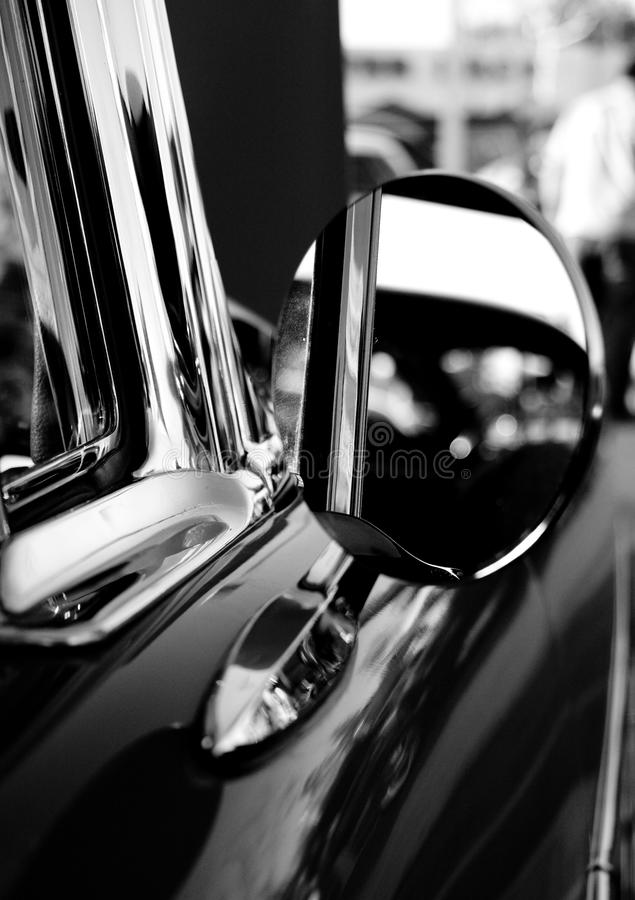 Vintage classic car chrome mirror. Classic collector car. Vintage hot rod at a car show. A detail view of the mirror in black and white royalty free stock photo