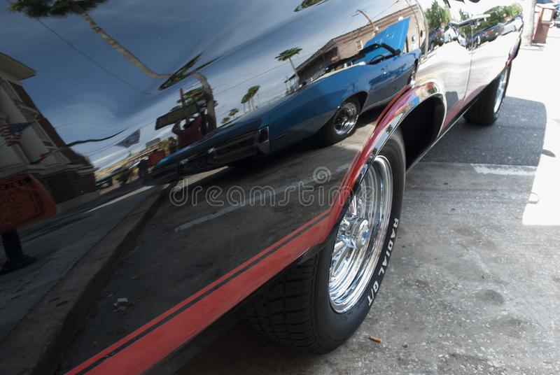 Vintage classic car with reflection of the street on its surface royalty free stock photo