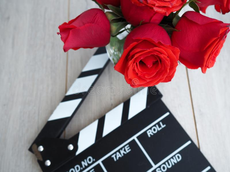 Vintage classic clapperboard on brown wooden table whis red roses.  stock photography