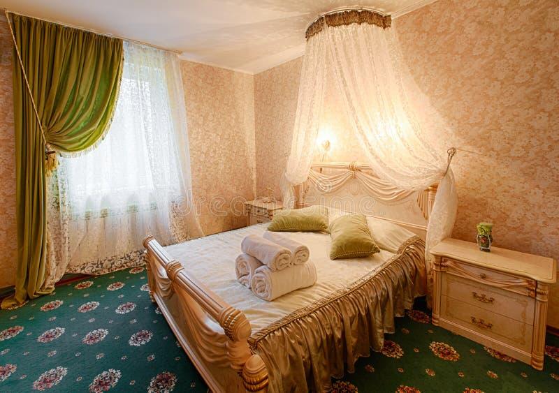 Vintage classic hotel bedroom interior. Bedroom interior design. Vintage bedroom, elegant and luxurious. Hotel premium luxurious classic interior. Double bed stock photo
