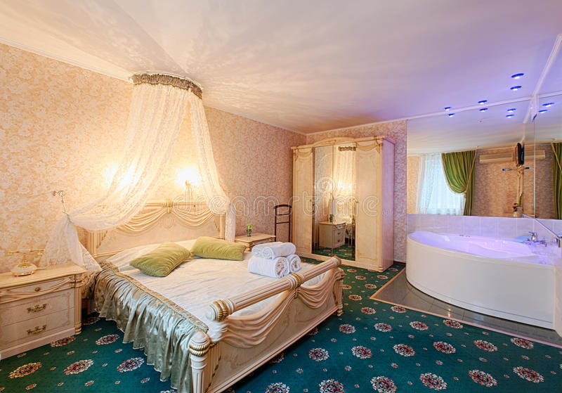 Vintage classic hotel bedroom interior. Bedroom interior design. Vintage luxurious bedroom premium suite with bath. Hotel classic interior. Double bed with stock photo