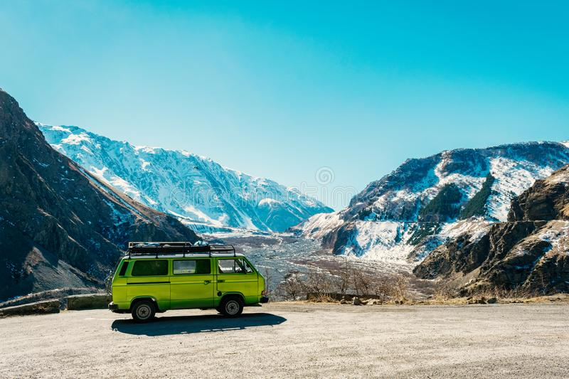 Caucasus Vintage classic van parked beside the road among the high Caucasus peaks on the far north of Georgia. Breath taking view stock photos