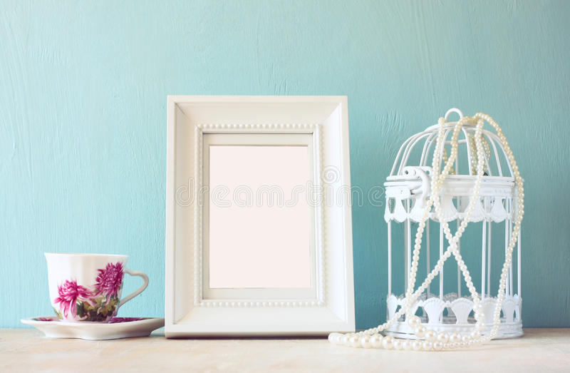 Vintage classical white frame on wooden table with porcelain cup and lantern.  stock photos