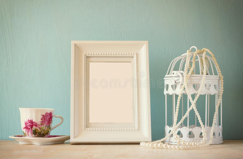 Vintage classical white frame on wooden table with porcelain cup and lantern stock images