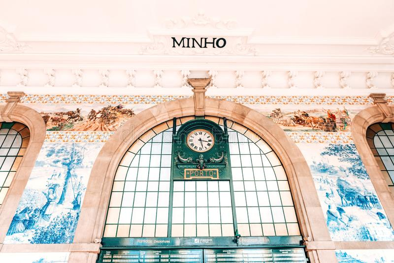 Vintage clock and decorative ceramic wall tiles in the main hall of Sao Bento Railway Station in Porto, Portugal. Vintage clock and Beautiful azulejos royalty free stock image
