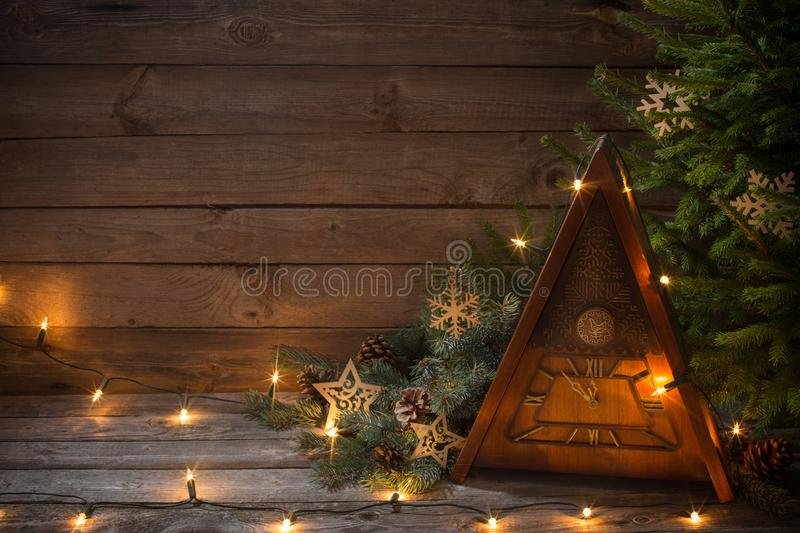 Vintage clock with Christmas tree on wooden background royalty free stock image