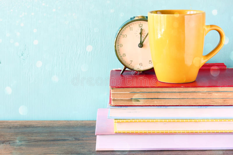 Vintage clock and cup over stack of books. royalty free stock images