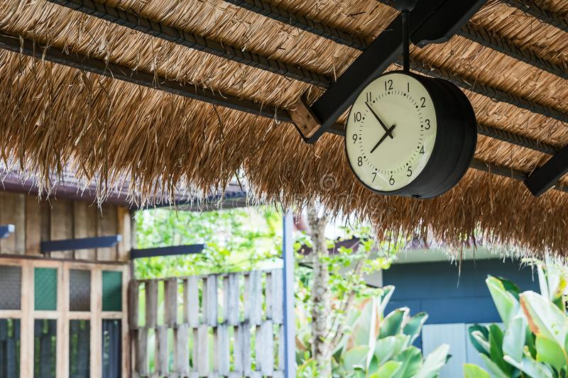 Vintage clock hung. The clock hung under the eaves stock photo