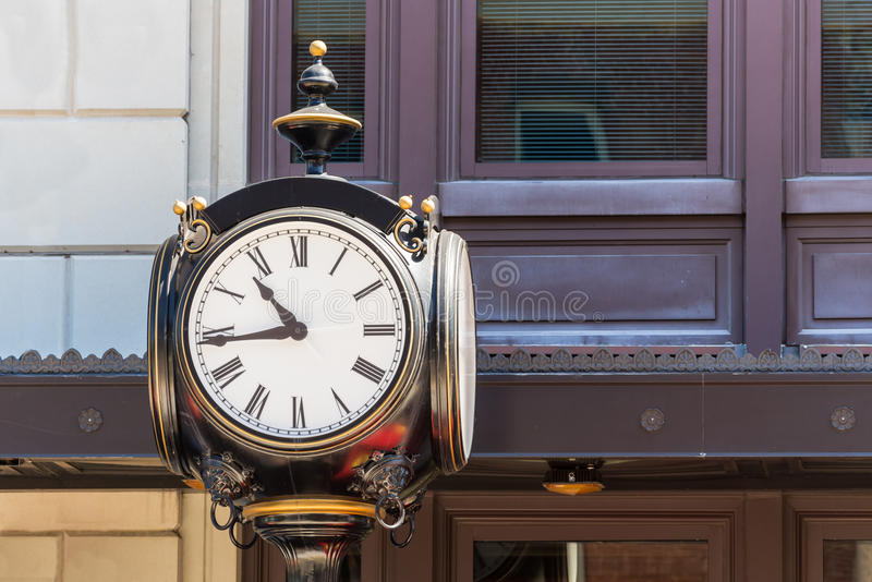 Vintage Clock on Lamp Post. Old Vintage Clock on top of a lamp post on the city street. Large clock face with analog hands stock photo