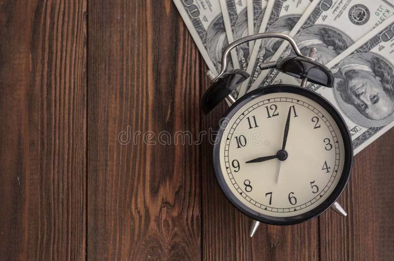 A vintage clock and money against a natural tree background. Tim royalty free stock images