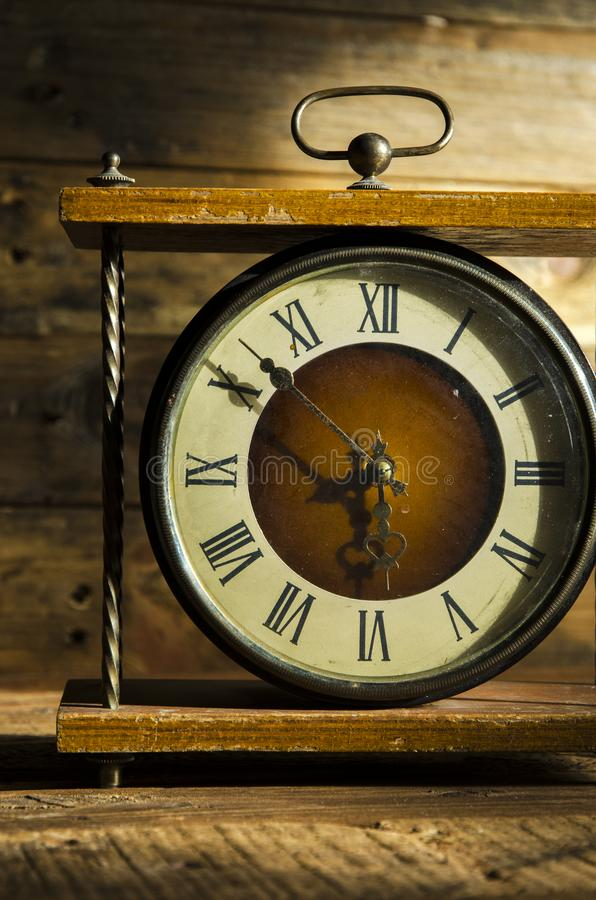 Vintage clock in the morning sun. Vintage clock on a wooden table in the morning sun royalty free stock photos