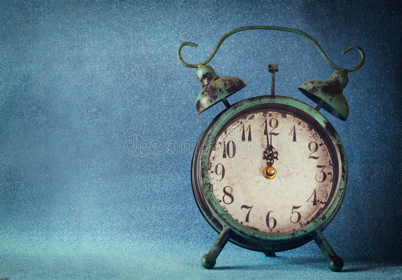 Vintage clock over blue ice bokeh background. new year concept. selective focus stock photography