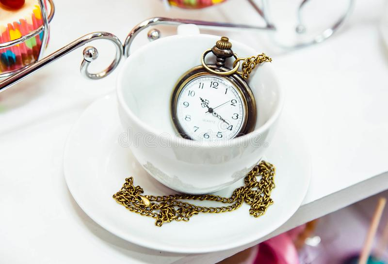 Vintage clock in a tea cup decoration in Alice in Wonderland style royalty free stock image