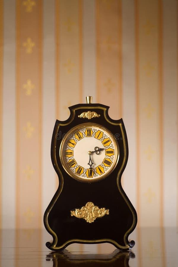 Vintage clocks on wallpaper background stock image