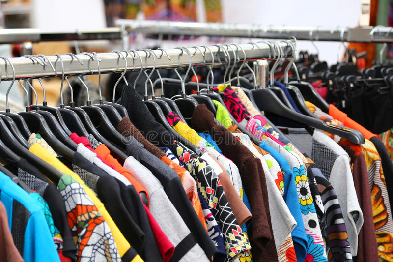 Vintage clothes of many colors for sale at flea market royalty free stock photography
