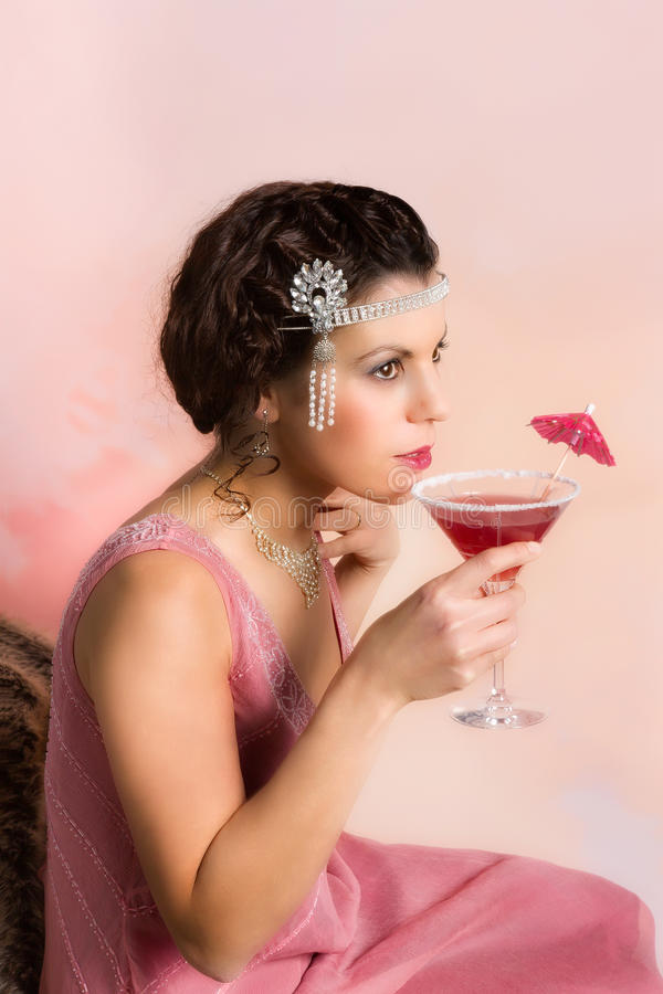 Vintage cocktail. Beautiful young vintage 1920s woman with headband and flapper dress drinking a cocktail royalty free stock images