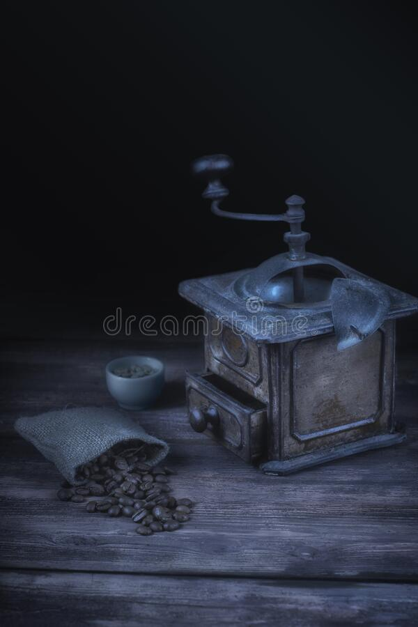 Vintage coffee grinder and bag of coffee beans. Moonlight style still life. royalty free stock image